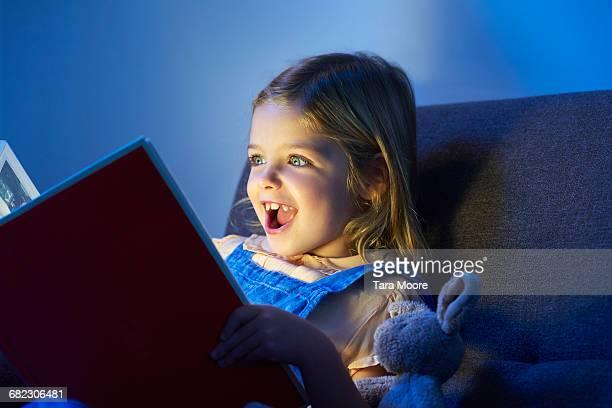 young girl looking excited reading book - 6 7 anos - fotografias e filmes do acervo
