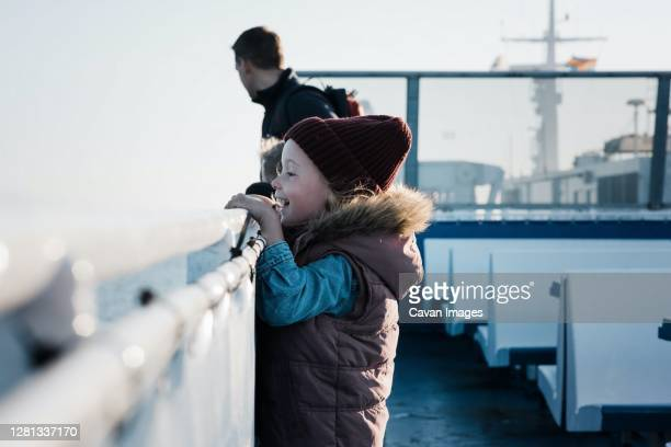 young girl looking excited whilst travelling on a ferry boat - ferry stock pictures, royalty-free photos & images