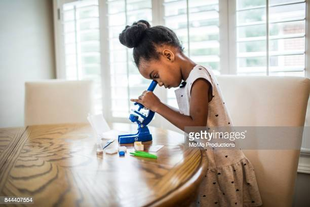 young girl looking in microscope - 女性科学者 ストックフォトと画像