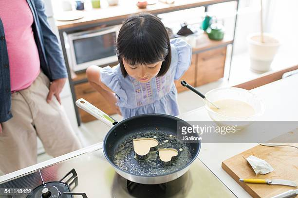 Young girl looking inquisitively into a frying pan