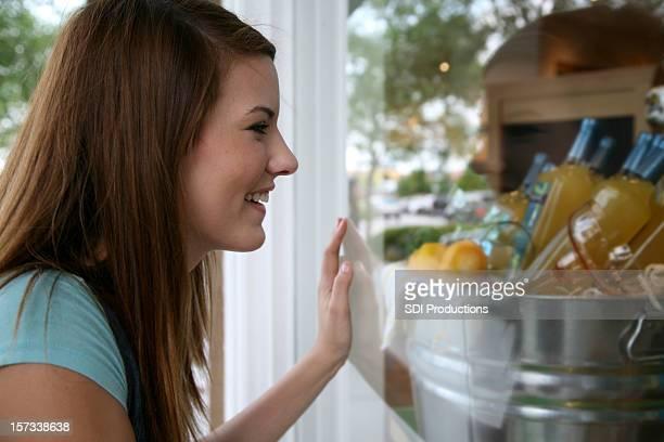 Chica joven mirando dentro de una tienda's Window