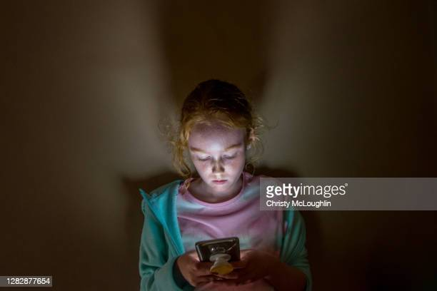 young girl looking into mobile phone screen, in dark room - online bullying stock pictures, royalty-free photos & images