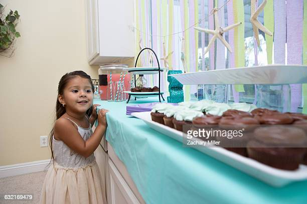 Young girl looking longingly at cakes on kitchen work surface