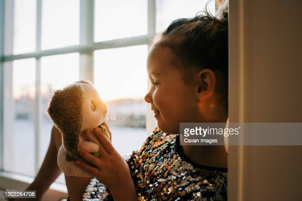 young girl looking lovingly at her toy at home at sunset - teddy bear stock pictures, royalty-free photos & images