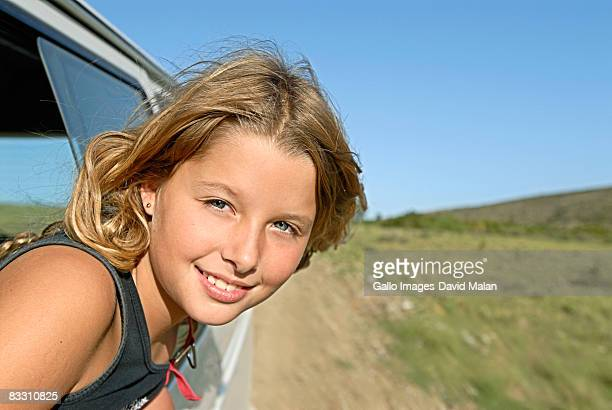 Young girl looking out a vehicle window.