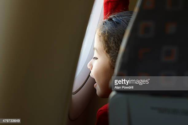 young girl looking out airplane window - aeroplane stock pictures, royalty-free photos & images