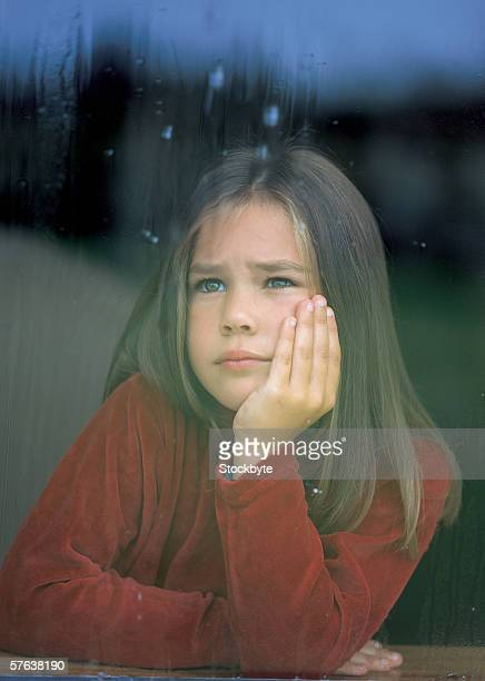 young girl (6-8) looking out of a window with a hand on her chin - sadgirl stock pictures, royalty-free photos & images