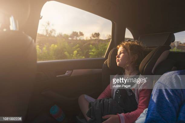 young girl looking out of car window - car stock pictures, royalty-free photos & images