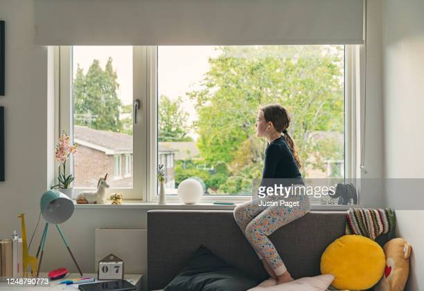 young girl looking out of her bedroom window - condition stock pictures, royalty-free photos & images