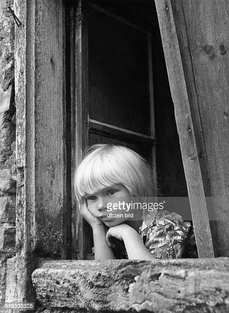 Young girl looking out of the window of an old house about 1955