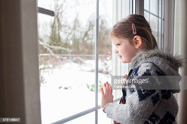 Young girl looking out of window at garden in snow