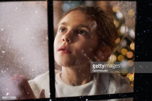 Young girl looking out of window, Christmas tree in background behind her, viewed through window