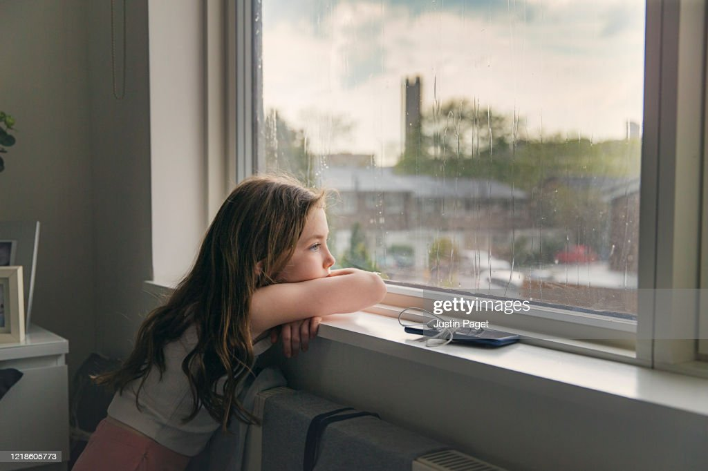 Young girl looking out of window on a rainy day : Stock Photo