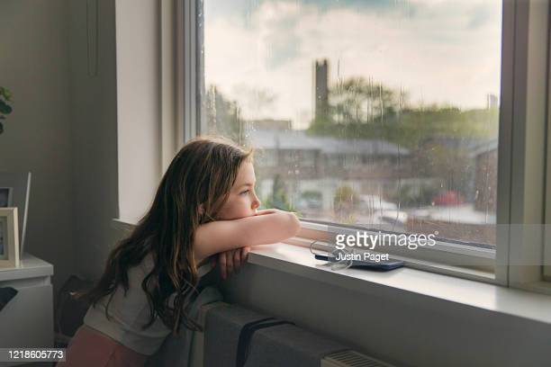 young girl looking out of window on a rainy day - verdriet stockfoto's en -beelden