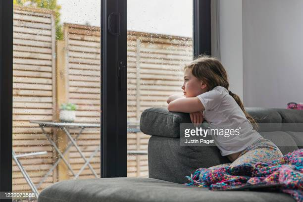 young girl looking out of window on a rainy day - solitude stock pictures, royalty-free photos & images