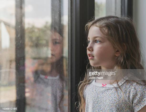 young girl looking out of window - sliding door stock pictures, royalty-free photos & images