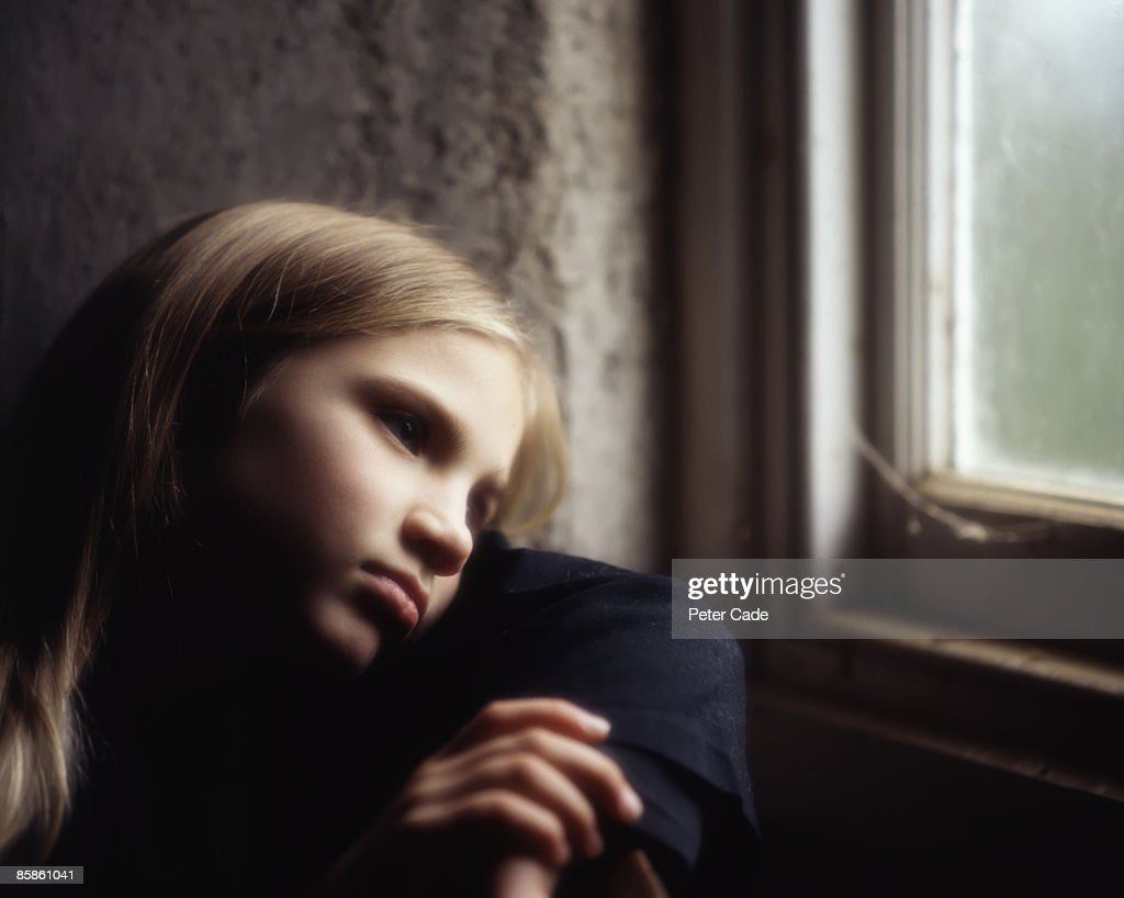 young girl looking out of window : Stock-Foto