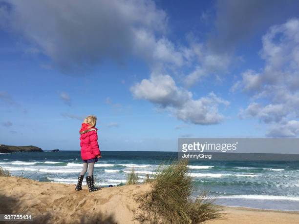 Young girl looking out to sea on beautiful spring day