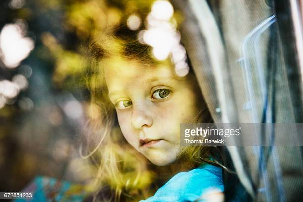 Young girl looking out window of camper van