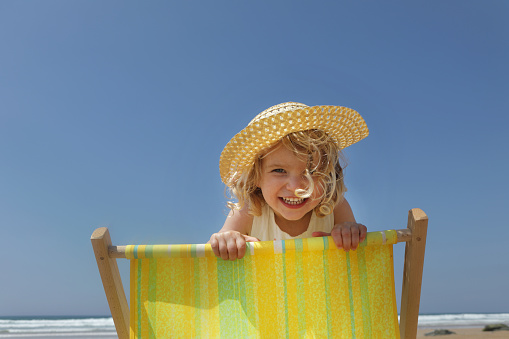 Young girl looking over back of deck chair on beach - gettyimageskorea