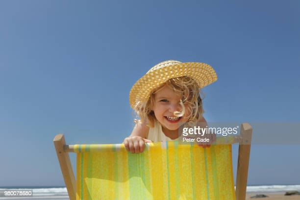 young girl looking over back of deck chair on beach - girls sunbathing stock pictures, royalty-free photos & images