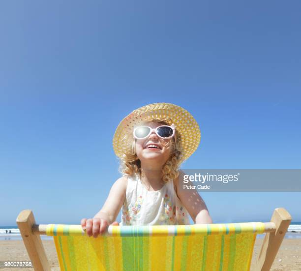 Young girl looking over back of deck chair on beach