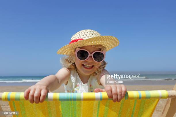young girl looking over back of deck chair on beach - sunglasses stock pictures, royalty-free photos & images