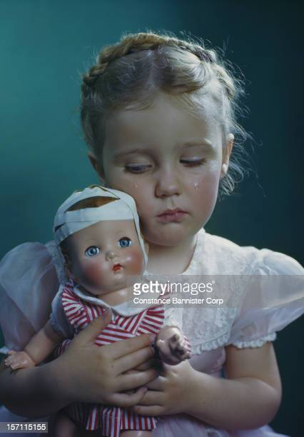 A young girl looking sad and holding her doll with bandages on its head 29th April 1946