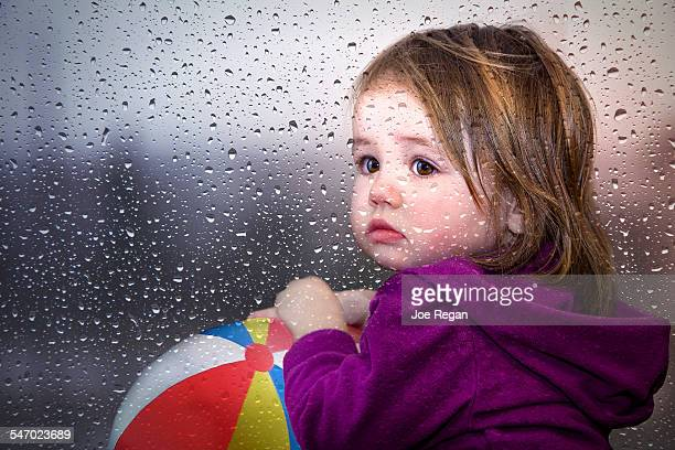 Young girl looking through a window of raindrops.