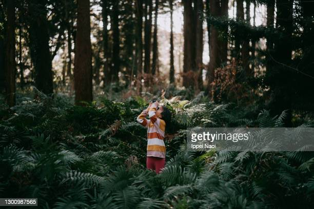 young girl looking through binoculars in forest in winter - binoculars stock pictures, royalty-free photos & images