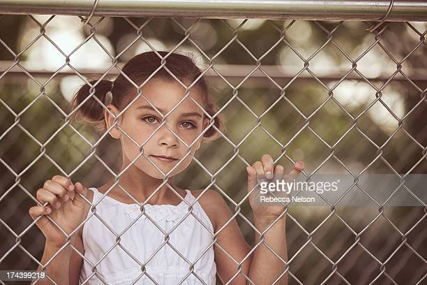 young girl looking through chain link fence