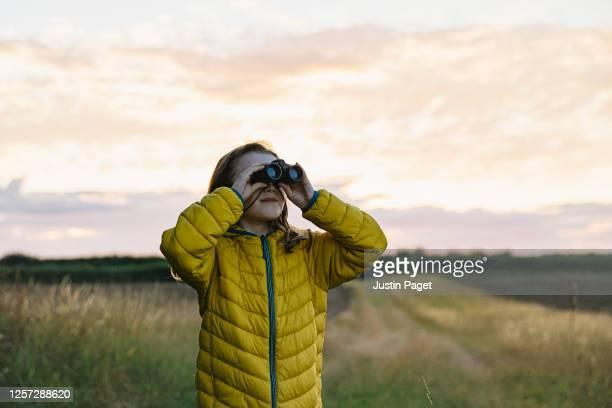 young girl looking through her binoculars - binoculars stock pictures, royalty-free photos & images
