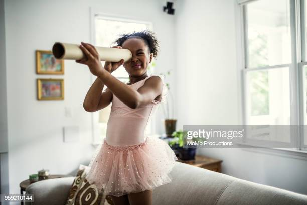 young girl looking through homemade telescope at home - curiosity stock pictures, royalty-free photos & images