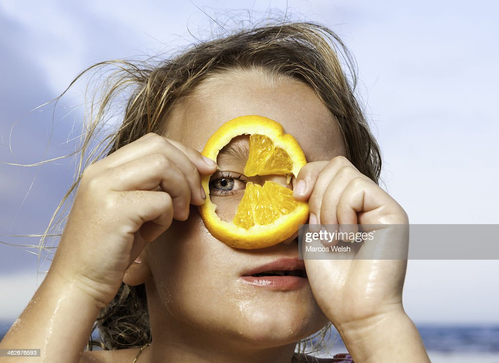Young girl looking through slice of orange : Stock Photo