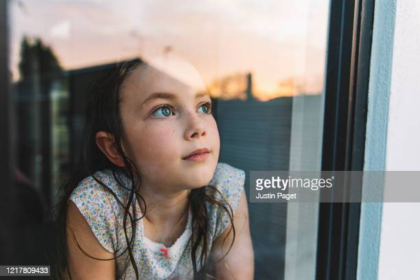 young girl looking through window at sunset - child stock pictures, royalty-free photos & images