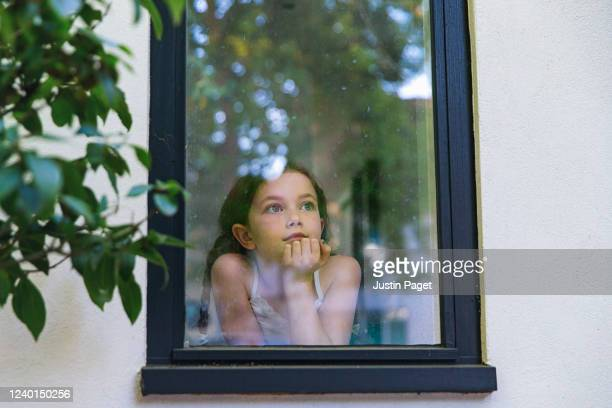 young girl looking through window - photographed through window stock pictures, royalty-free photos & images