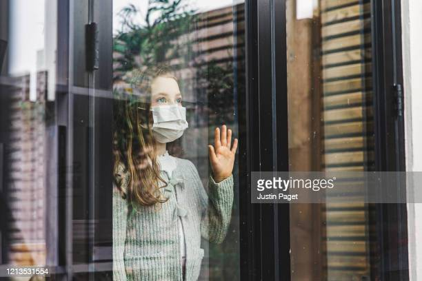 young girl looking through window with mask - abstand halten infektionsvermeidung stock-fotos und bilder