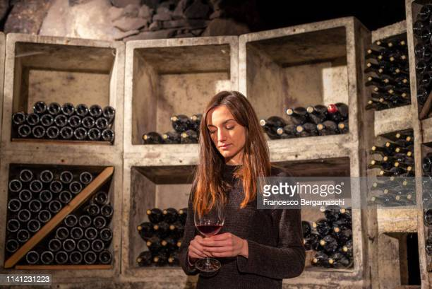 young girl looks a wine glass in the cellar. mese, valchiavenna, valtellina, lombardy, italy, europe. - italia stock-fotos und bilder