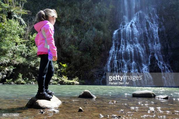 Young girl looks at a waterfalls in New Zealand
