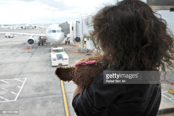 Young girl looks at airplane while waiting for her flight