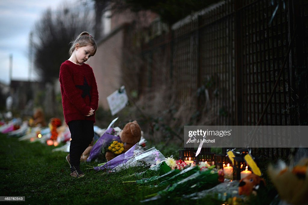 A young girl looks at flowers and candles laid by members of the public near to the house in Ferry Gait Crescent where three year old Mikaeel Kular was reported missing last Thursday on January 19, 2014 in Kirkcaldy, Scotland. Rosdeep Kular, 33, the mother of three-year-old Mikaeel Kular, has been charged over the death of her son.