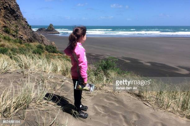young girl looks at karekare beach new zealand - rafael ben ari - fotografias e filmes do acervo