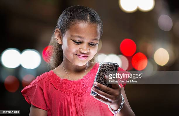 Young girl looks at mobile phone in evening.