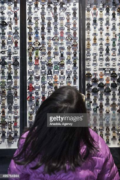 Young girl looks at Star Wars figures displayed outside a shopping mall ahead of the release of the film in Hong Kong on December 3, 2015. The new...