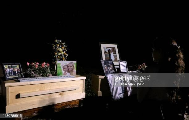 TOPSHOT A young girl looks at the coffins with the remains of Rhonita Miller and four of her children who were among the nine victims killed on...
