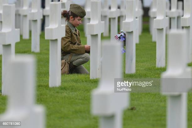 Young girl looks at the graves of fallen soldiers at the Normandy American Cemetery that contains the remains of 9,387 American military dead, most...