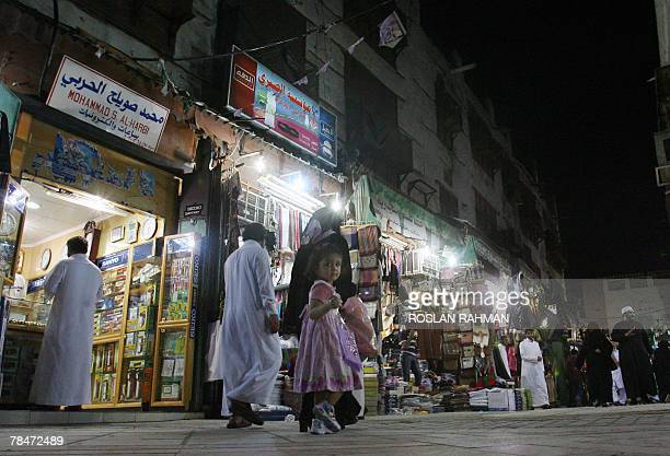 A young girl looks back while walking with her mother along a street in an old market of the ancient Saudi city of Balad in the Red Sea city of...