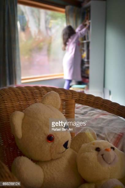 young girl looks for a book in her bedroom - rafael ben ari stockfoto's en -beelden