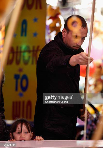 A young girl looks on as her companion tries to hook a duck on a fair ground stall at the annual Goose Fair on October 6 2010 in Nottingham England...
