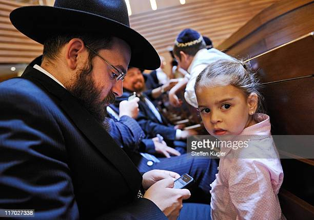 A young girl looks on as her father checks his iPhone prior to an ordination ceremony for six rabbinical students at Gedola Yeshiva at the Chabad...